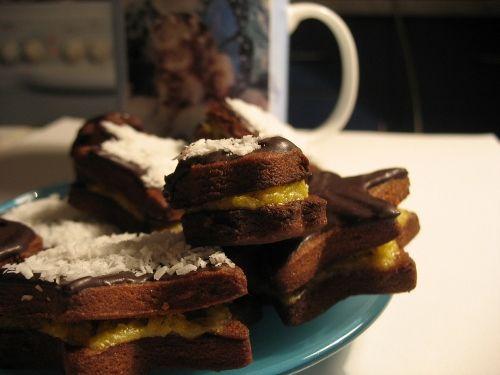 Шоколадно-кокосовое печенье.  Для теста: 250 г муки 25 г какао 100 г сахарной пудры щепотка соли 200 г охлажденного сливочного масла 2 желтка 1 ч. л. разрыхлителя  Для крема: 3 желтка 50 г сахара 20 г муки 200 г горячего молока 40 г кокосовой стружки  Для помадки: 5-6 ст. л. какао 30 г сливочного масла 3-4 ст. л. сахара 40-50 г сливок 22%-33%  Для украшения: кокосовая стружка