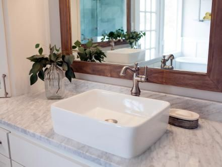 The new master bath is one of the most potent examples of the blending of styles, with clean marble countertops and matching white vanities offset by wood surfaces in natural finish as seen in the framed mirror seen here.