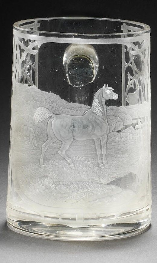 A Bohemian engraved mug by Franz Paul Zach, circa 1860 Of slightly tapering cylindrical form, the front panel finely engraved with a horse standing alertly in a meadow, other horses behind and an extensive landscape in the distance, the panel framed with Gothic ornament formed from branches and panels of vacant shields, the engraving signed with the initial Z., 14.4cm high