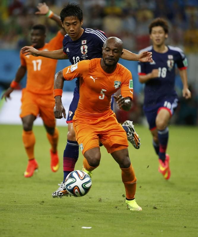 Japan's Shinji Kagawa fights for the ball with Ivory Coast's Didier Zokora (front) during their 2014 World Cup Group C soccer match at the P...
