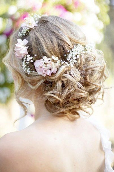 Curly wedding hairstyle with flowers. No wreath of flowers, maybe just above where the hair is gathered