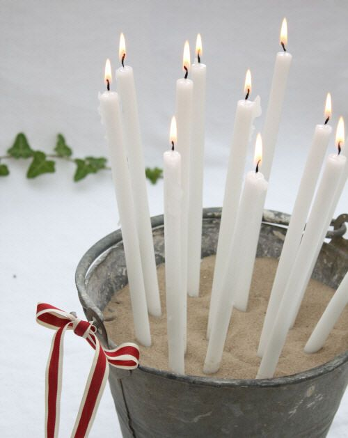 white candles in zinc bucket with red ribbon :: a casual candle holder for an outdoor get-together!  nice!  : ) things it looks like you would you need:  candles, sand, a metal bucket and your ribbon of choice.