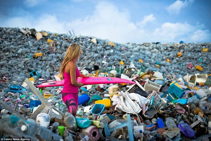 Dark side of paradise: Alison Teal pictured with her surfboard while walking through mountains of rubbish onThilafushi in the Maldives