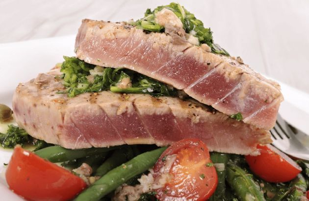 Ahi Tuna (Yellowfin) Steaks Grilled with a Mediterranean Flair.  Yellowfin Tuna or Ahi Tuna is usually served either Raw, as in sushi or Seared. or Grilled.   When I first had this tuna grilled in spain with olive oil and salt I couldn't believe it was fish at all.  This recipe is a bit of a cross between seared italian style and Spanish grilled.