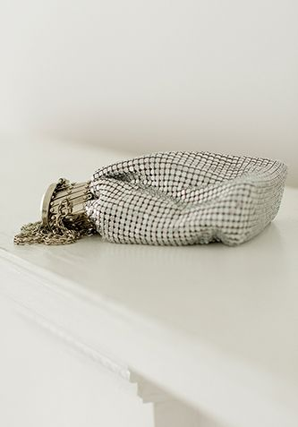 Silver-colored brass mesh flask purse with grey-colored lining. The opening expands to fit credit cards, cash, keys, and small cell phones. Perfect for a night out!