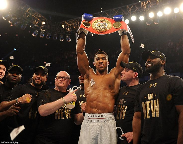 British boxer Anthony Joshua holds the IBF world heavyweight belt up high as he poses for pictures after defeating Charles Martin