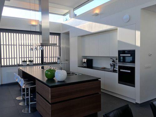 Een moderne keuken met een mooie combinatie van hout, zwart en wit. Keukendealer: www.wildhagen.nl