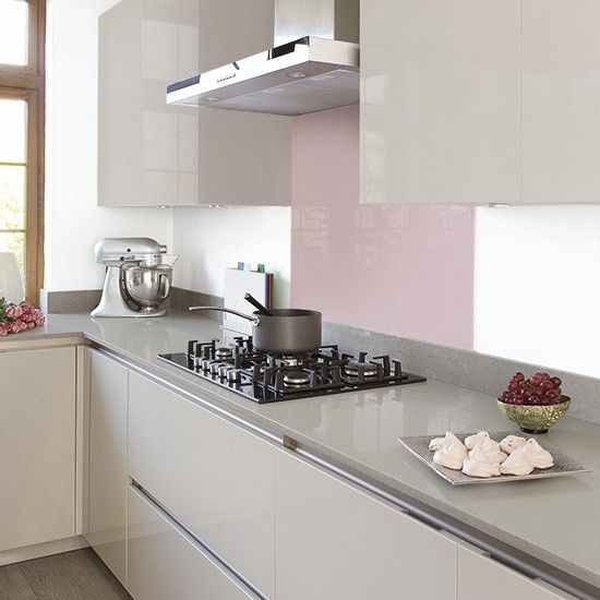 Grey modern kitchen with handleless cabinetry and pink splashback
