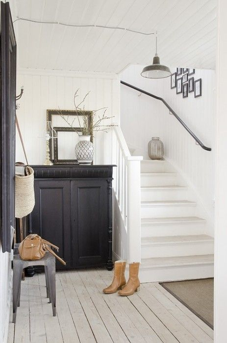 Schifano - entry, white stair, iron rail, square pendant, dresser at end of stair, long mirror end of hall.