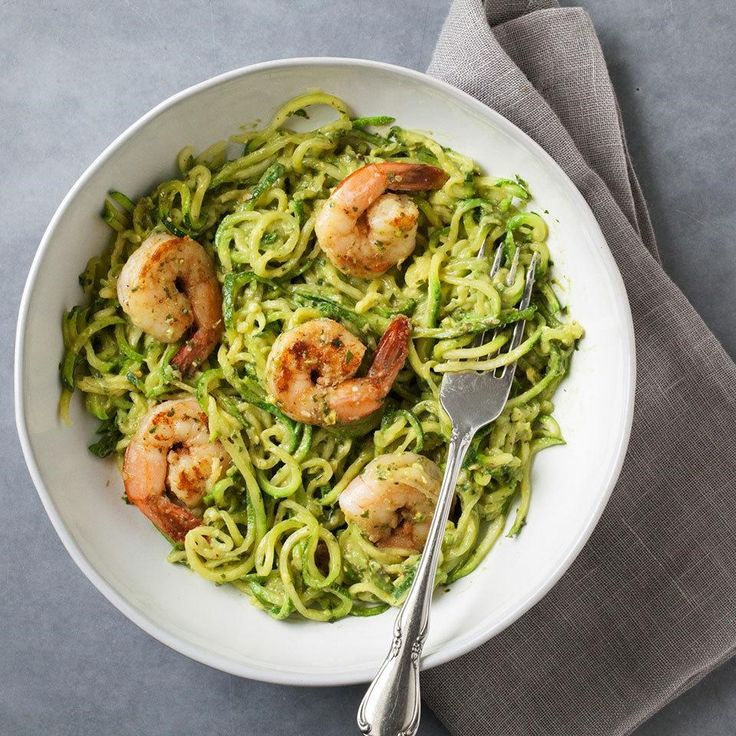 Cut some carbs and use spiralized zucchini in place of noodles in this zesty pesto pasta dish recipe. Top with Cajun-seasoned shrimp to complete this quick and easy dinner. #cleaneating