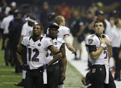 Baltimore Ravens quarterback Joe Flacco (5), wide receiver Jacoby Jones (12) and linebacker Adrian Hamilton (54) watch the field during a power outage at the Superdome in the second half of the NFL Super Bowl XLVII football game against the San Francisco 49ers, Sunday, Feb. 3, 2013, in New Orleans. (AP Photo/Elaine Thompson)