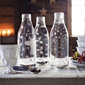 Bouteilles de verre peintes de flocons, étoiles et feuilles de houx en blanc