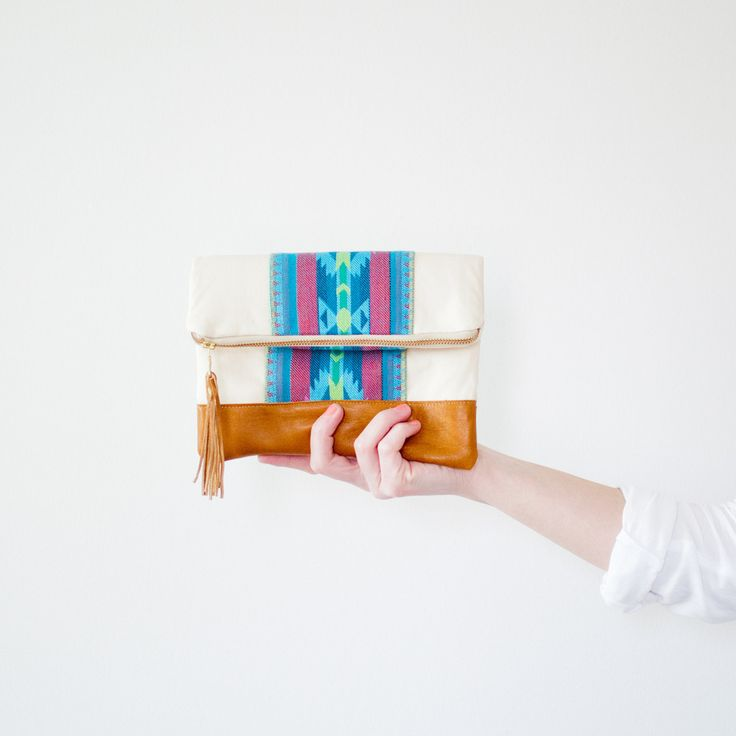 Aztec print clutch has turquoise Aztec pattern and genuine lambskin leather base and tassel. Measures approx. 9 inches by 10 inches wide. Cotton lining, and brass metal zipper. *handmade in the USA by