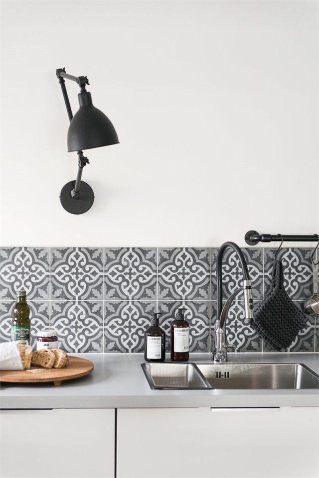 Et nous en avons encore la preuve avec cette séduisante cuisine, et sa crédence en tons gris, noir et blanc qui s'accordent parfaitement avec les chaises Tolix en acier et les appliques noires métalli