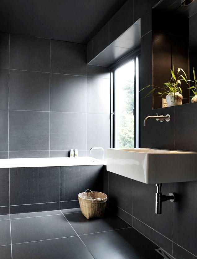 Minimalistic bathroom design with black tiles in the walls and surrounding the bathtub |  #luxurybathrooms #homedecorideas #bathroomideas