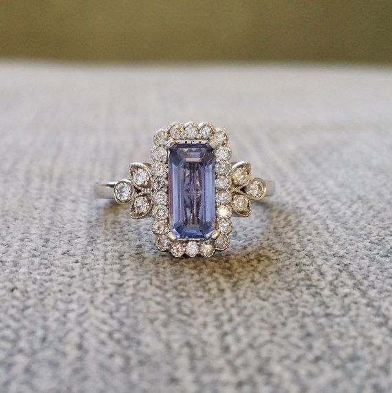 This Stunning Ring features a 14K White Gold Diamond Halo Setting. Set with an Amazing .80 Carat Emerald Scissor Cut Light Blue Sapphire and .30