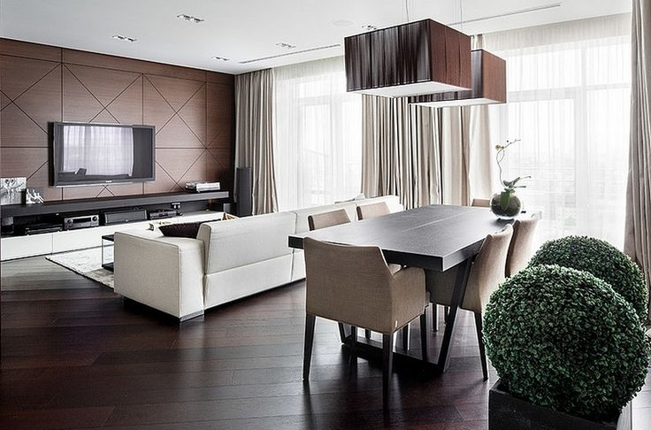 Open Living And Dining Area On Wooden Floor With Decorative Wall Panel And White Sofa Also Black Wooden Dining Table With Lovely Seats And Stylish Hanging Lamps Decor Modern interior of an apartment with lots of wooden parts http://seekayem.com