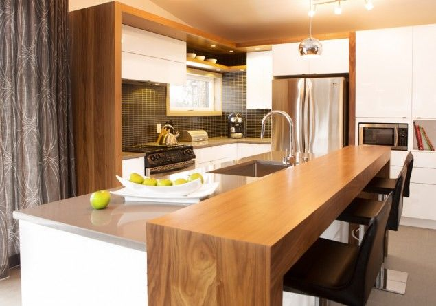 Nous retrouvons dans cette cuisine l'agencement de 2 tons. La cuisine a été réalisée en thermoplastique blanc lustré avec une insertion de placage de noyer. Le tout harmonisé avec un comptoir de quartz.