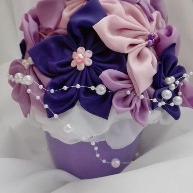 <br/>Ikebanka vyrobená z 3 odtieňov fialovej a ružovej látky. Kvietky sú ručne šité, dozdobené perličkami. Je použitých cca 20 kvetov. Na oživenie je
