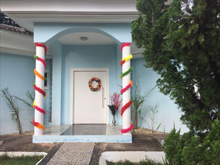 E a entrada da casa ficou assim: usei colares havaianos de tecido e fiz a guirlanda com flores de tecido sobre uma base de palha da costa.