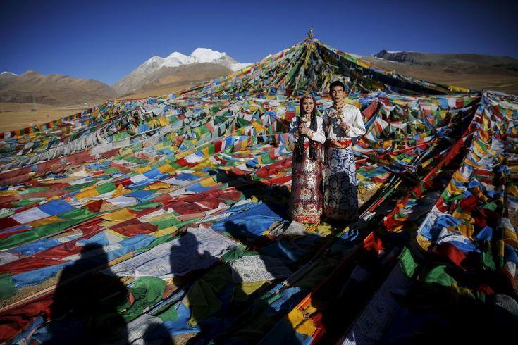 La pareja de la foto se acaba de casar. Son Jing Li, de 22 años, y su marido, Ke Xu, de 23, ambos originarios de la ciudad de Shiyan, en la provincia de Hubei, al noroeste de China. Llevan tres años viviendo en el Tíbet, y posan sonrientes para el álbum de boda con los trajes tradicionales de la región. Les rodea una alfombra multicolor de banderines de oración, una ofrenda habitual entre los budistas del Himalaya, en el puerto de Tanggula (5.072 metros, 262 metros más que la cumbre del…