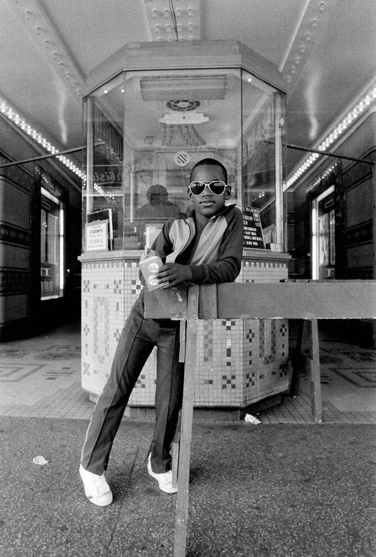 A boy in front of the Loews 125th Street movie theater, Harlem; 1976