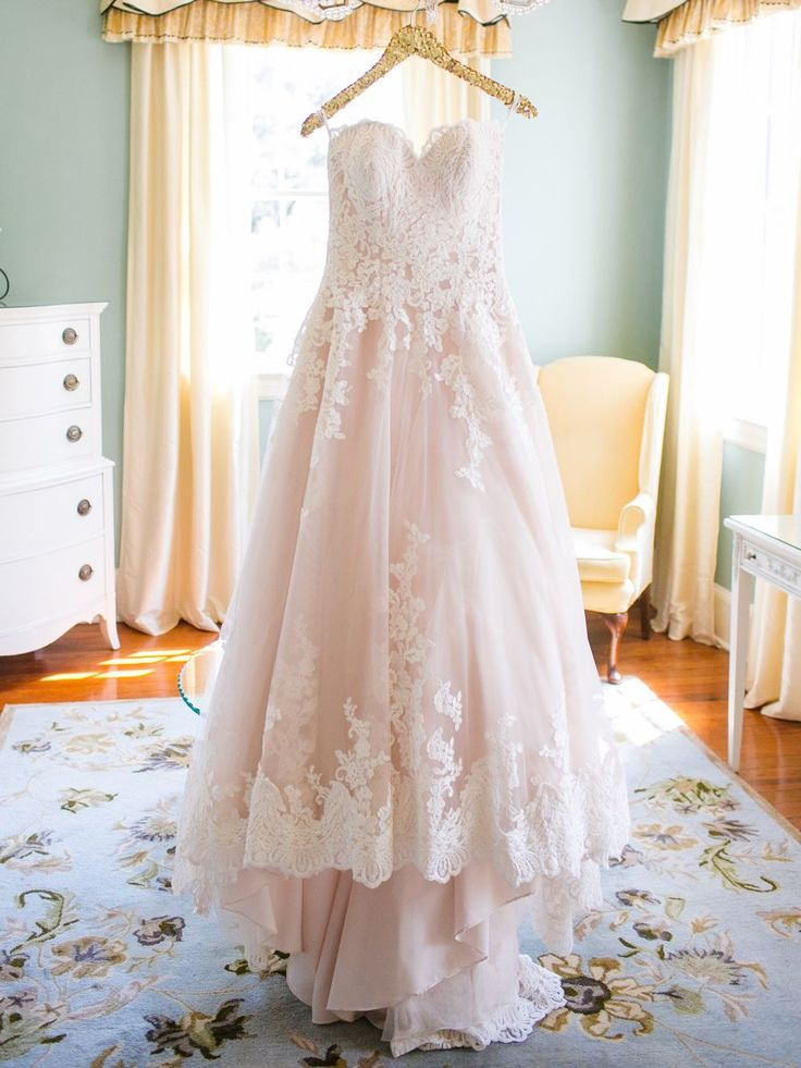 Rock a strapless sweetheart wedding dress with a subtle pink tone for a colorful bridal style.