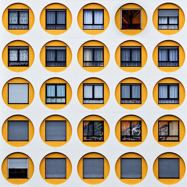 This exterior space contains repeating yellow circles around the windows; the yellow circles have repitition