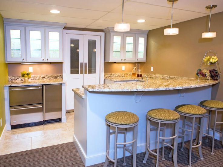 This basement bar is topped with a heavy slab of marble and lit by three contemporary pendant lights. A stainless steel mini fridge and glass-front cabinets make sure the bar stays well-stock and equipped for entertaining.