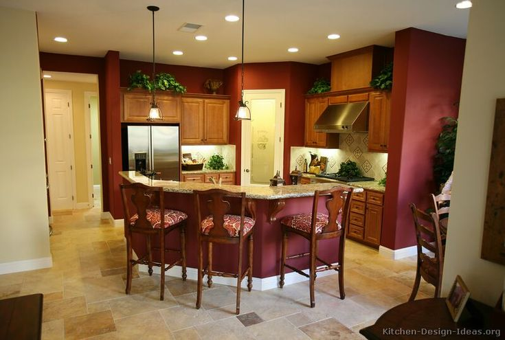 #Kitchen Idea of the Day: Golden-brown kitchen cabinets with maroon colored walls and neutral travertine tile flooring.