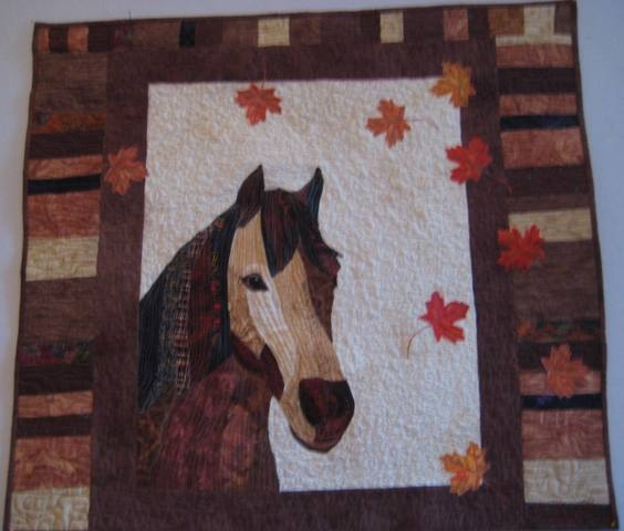 "I made the horse from a pattern by Sharon Malec, added a border to resemble a stable, and autumn leaves.  Named this quilt ""Change of Season""  Jeanne Turner McBrayer"