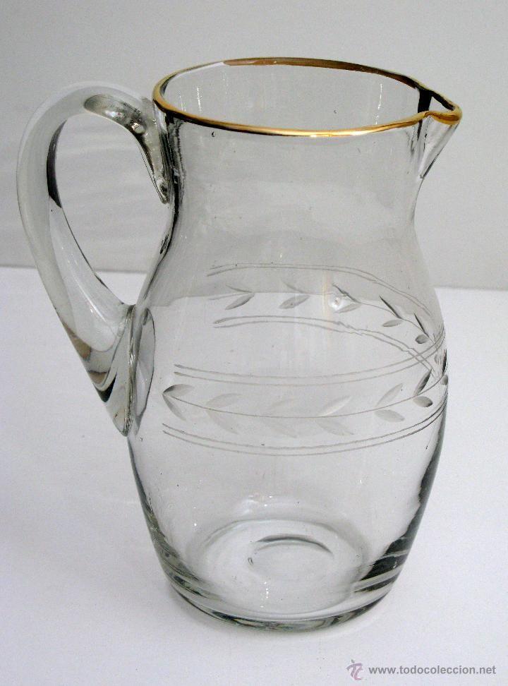 Antigua jarra de agua en cristal tallado y dorado.