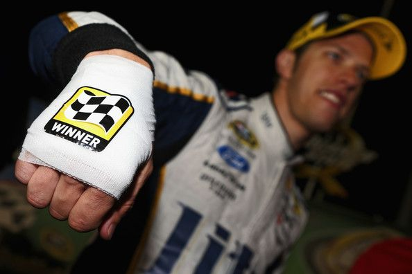 Brad Keselowski, driver of the #2 Miller Lite Ford, shows his bandaged hand after cutting himself while celebrating with champagne in Victory Lane after winning the NASCAR Sprint Cup Series Quaker State 400 presented by Advance Auto Parts at Kentucky Speedway on June 28, 2014 in Sparta, Kentucky.