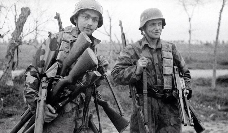 Two German soldiers with captured American M1 Garands and Thompson submachine guns, 1944.