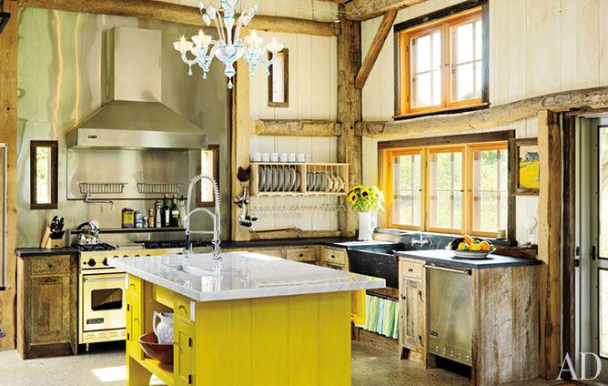 Rustic beams mixed with a vibrantly painted Shaker style island, Murano glass chandelier, and modern stainless steel appliances.  Amazing mix of rustic and modern.