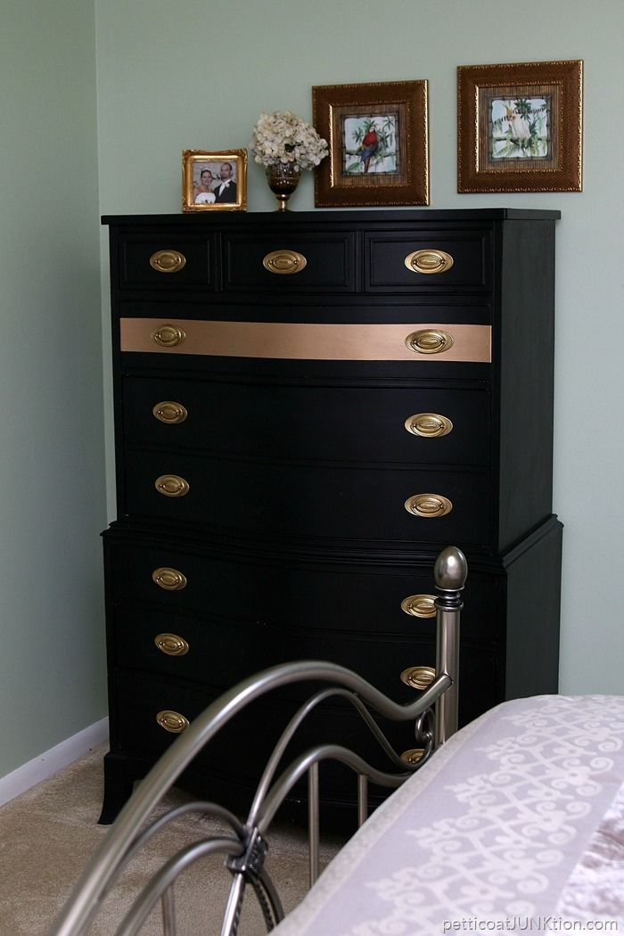 Furniture makeover. The chest of drawers is painted black. I spray painted a gold stripe across one of the drawer and cleaned the original hardware with Barkeepers Friend. Before and after photos with a tutorial on the blog.