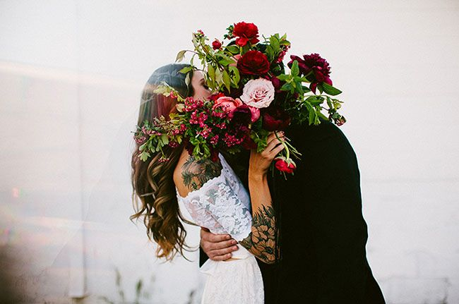 Cute wedding shot: huge bouquet of beautiful flowers in front of the bride and groom's faces as they kiss