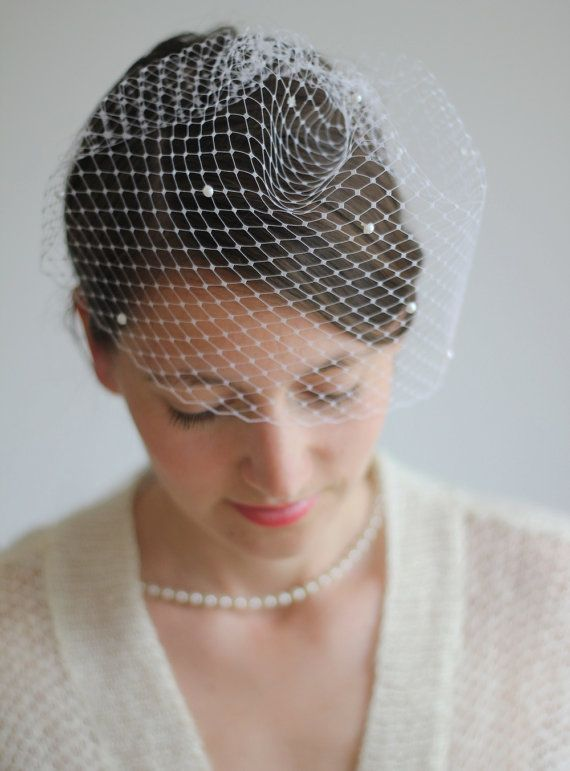 This pearl veil could be a lovely vintage-inspired addition to your bridal outfit. It is attached to a silver tone metal comb for an easy fit. This