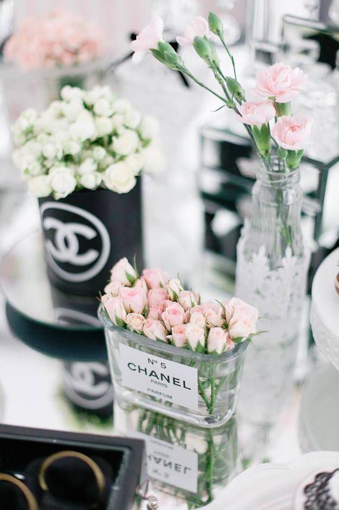 Pretty pink and white flowers arranged alongside Chanel -- a super cute way to repurpose old packaging