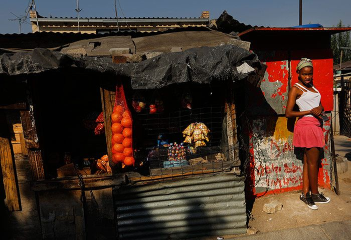A girl who has just finished school stands near a small shop selling fruits, sweets and crisps. Credit: Kim Ludbrook/EPA