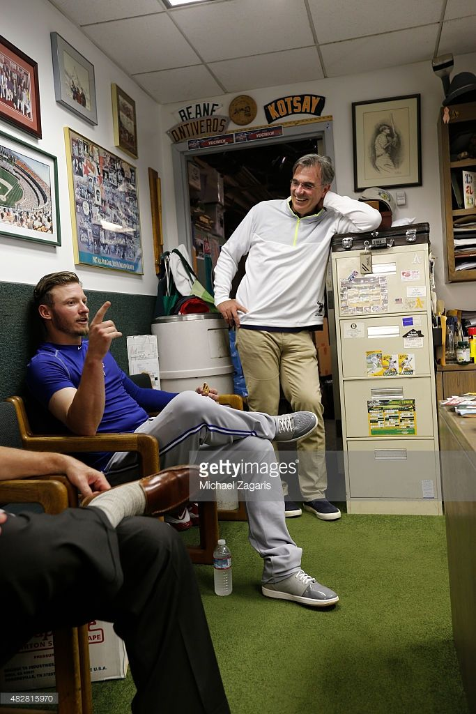 General Manager Billy Beane of the Oakland Athletics talks with Josh Donaldson #20 of the Toronto Blue Jays in the Athletics clubhouse prior to the game between the Athletics and the Blue Jays at O.co Coliseum on July 21, 2015 in Oakland, California. The Blue Jays defeated the Athletics 7-1.