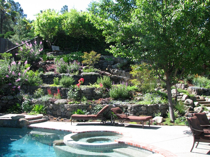 Layered retaining walls provide planting opportunities, slowing runoff, steps provide access.