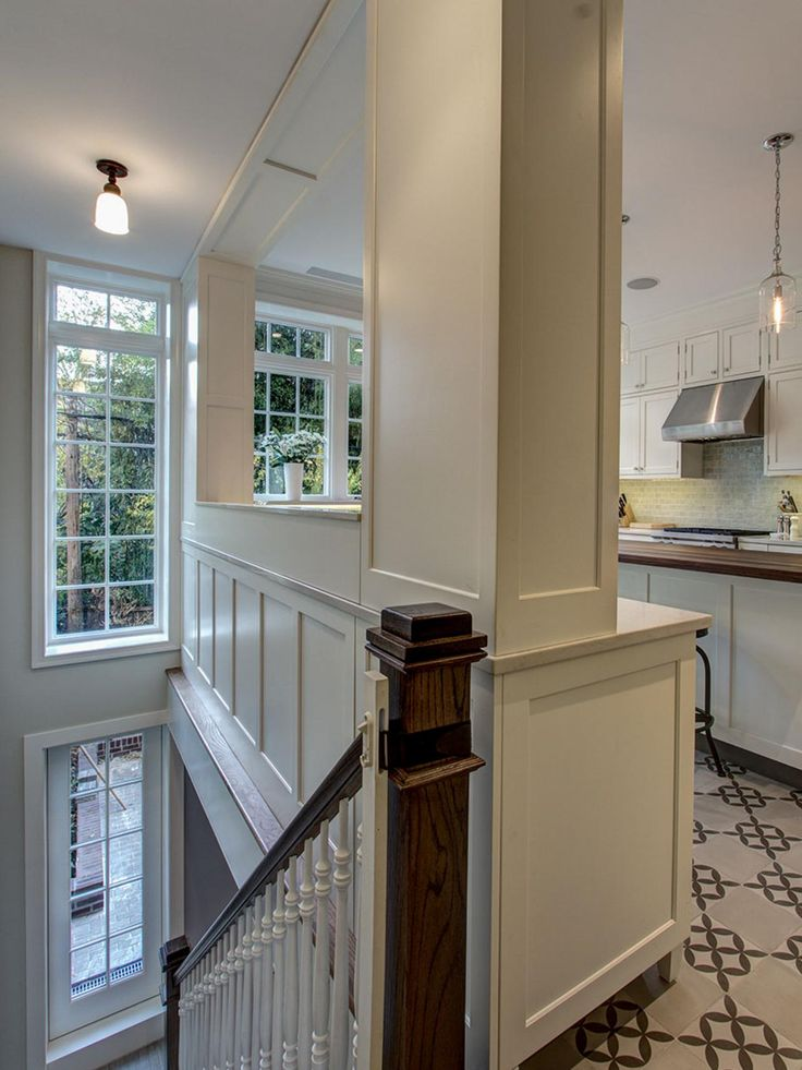 The stairway to a lower-level family room backs up to the traditional kitchen in this Brooklyn townhouse. A wide pass-through window opens up the space, bringing in lots of natural light and giving an airy feel to what could otherwise be a cramped galley kitchen.