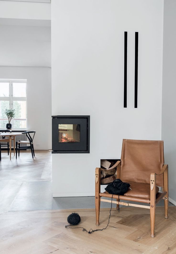 Living room with a cozy fireplace and a classic Safari armchair from Kaare Klint.