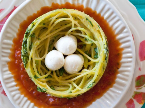 """In Giada's adorable Spaghetti Nests, bocconcini (small, fresh mozzarella balls) stand in for birds' eggs. Use tongs to swirl the cooked spaghetti, then transfer it to a prepared pan and bake until firm enough to hold the """"eggs."""""""