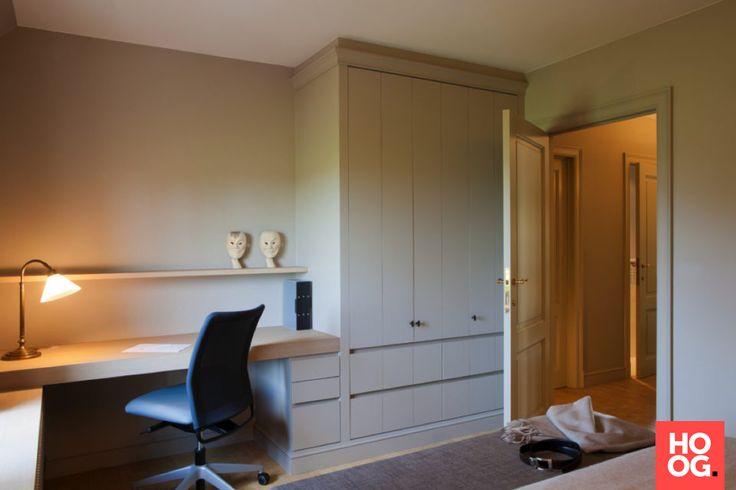 Luxe slaapkamer met op hout gemaakte kasten en werktafel