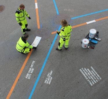 Tom H. Jensen, Rune Rørheim og Kåre Olsen i vann- og avløpsverket malte rør og en hilsen til byens befolkning i en av Stavangers gater. Seansen ble fotografert, og materialet skal brukes i informasjonsmateriell.