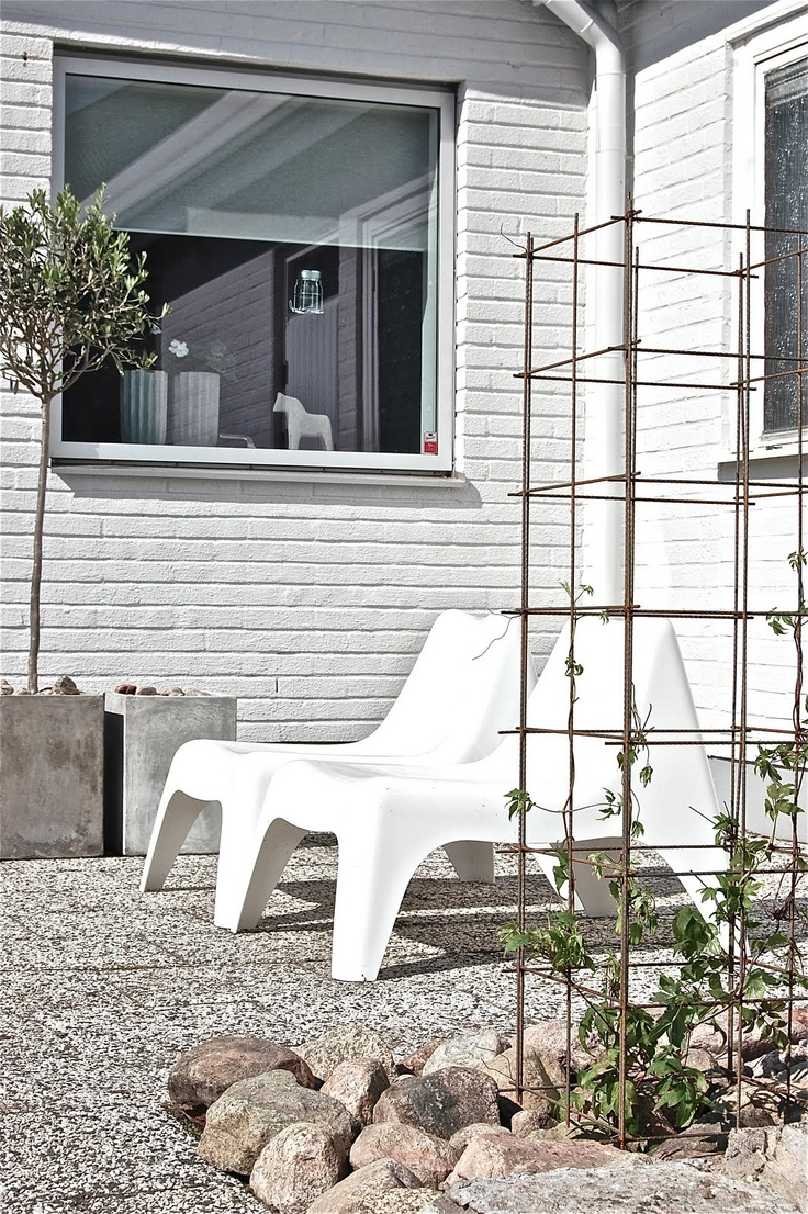 white Ikea ps chairs + olive tree in square cement pot + awesome exterior flooring