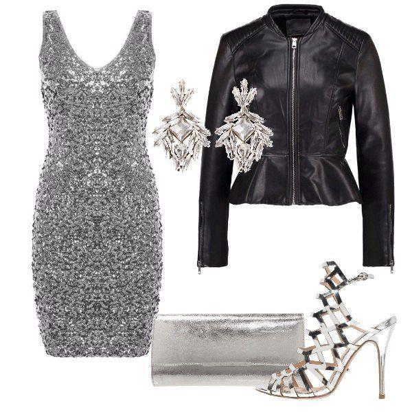 L'outfit è composto da un abito aderente color argento coperto di paillettes e la giacca in similpelle con balza sul fondo. La pochette, il sandalo elaborato e gli orecchini con cristalli danno ulteriore luce al look.