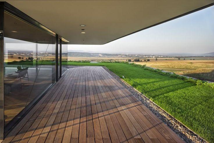 Terrasse couverte en bois devant de grandes baies vitrées de cette maison d'architecte